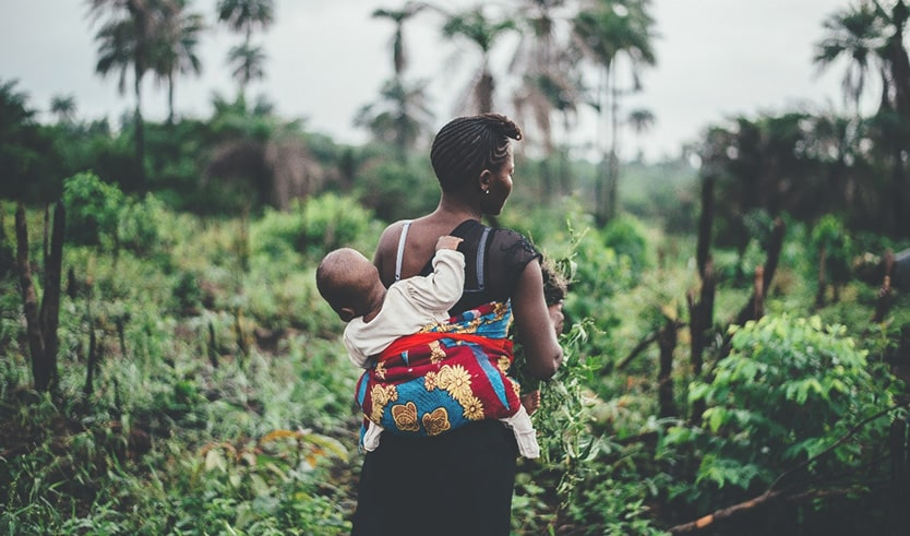 A women walking through a field carrying a baby on her back